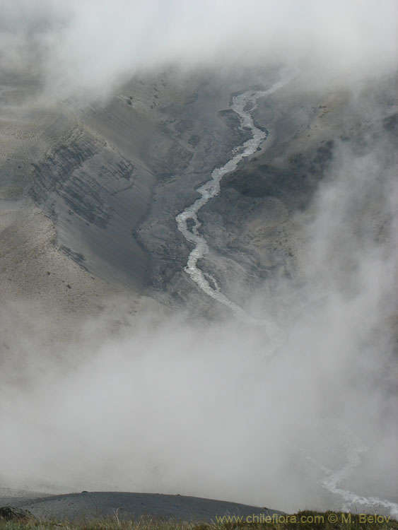 An  image of a river flowing, viewed from above through the clouds, Mondaca Trail, Radal Siete Tazas National Park, Chile.