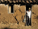 An image of an Adobe House with a Man