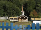 Image of a traditional wooden church behind locked wooden gate near Coñaripe, Chile.